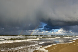 Regenboog aan de onderkant van een hagelbui op het strand van de Noordduinen bij Callantsoog