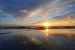 Warme gloed van zonsondergang weerspiegelt in het ondiepe zeewater langs de vloedlijn op het strand van Wijk aan Zee.