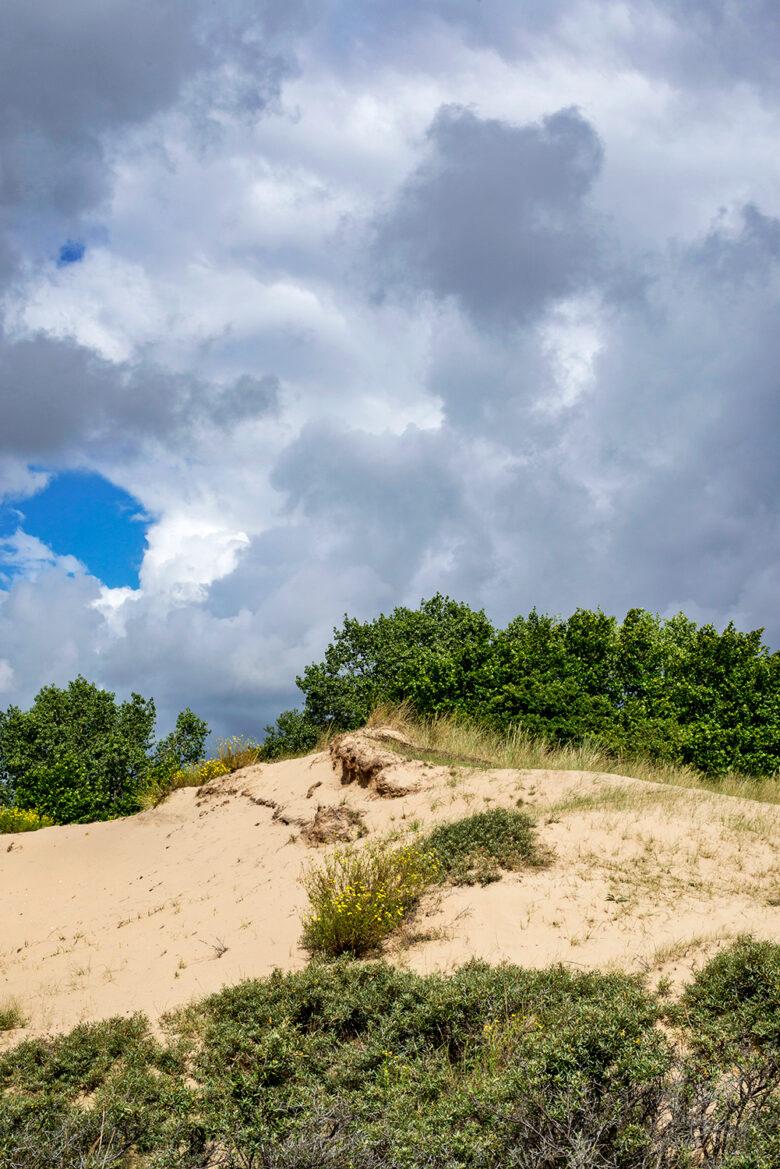 Wolkenlucht boven zanderige duinhelling van een stuifkuil in de Amsterdamse Waterleidingduinen bij Zandvoort.