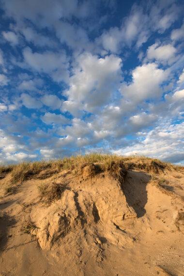 Schapenwolken boven zanderige duinhelling van stuifkuil in de duinen van het Noordhollands Duinreservaat bij Wijk aan Zee.