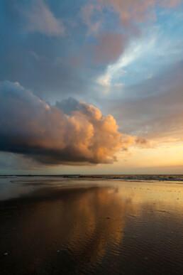 Warme gloed van ondergaande zon schijnt op wolken tijdens zonsondergang op het strand van Wijk aan Zee.
