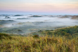 Uitzicht vanaf duintop over lagen mist tussen duinen tijdens zonsopkomst in het Noordhollands Duinreservaat bij Egmond aan Zee.
