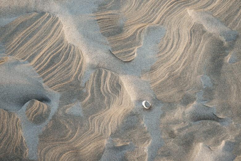 Door de wind uitgeslepen zandstructuren aan de voet van de zeeduinen op het Kennemerstrand bij IJmuiden.