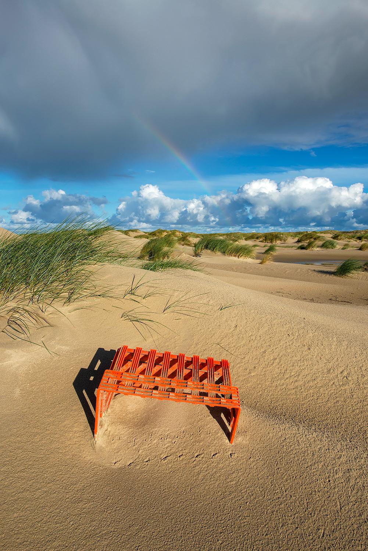 Aangespoeld oranje plastic krat aan de voet van de duinen op de strandvlakte van De Hors van waddeneiland Texel