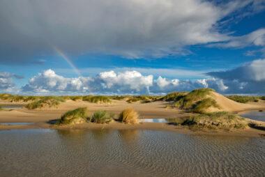 Regenboog boven natte vallei tussen de zeeduinen op de strandvlakte van De Hors op de zuidpunt van Waddeneiland Texel.