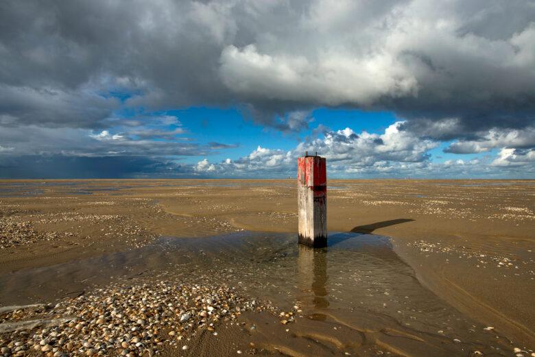Donkere wolken boven een rood gekleurde houten strandpaal op de lege strandvlakte van De Hors op de zuidpunt van Waddeneiland Texel.