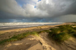 Harde wind en dreigende wolkenluchten boven zee tijds zonsopkomst op het strand van Wijk aan Zee
