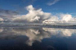 Weerspiegeling van wolkenlucht boven de Noordzee in het ondiepe zeewater langs de vloedlijn op het strand van Wijk aan Zee.