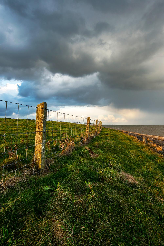 Donkere wolkenlucht van regenbui boven de dijk en Waddenzee bij het dorpje Vatrop op voormalig Waddeneiland Wieringen.
