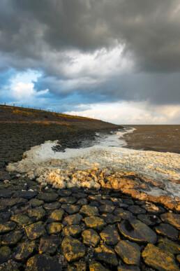 Donkere wolken boven aangespoeld schuimalg (Phaeocystis globosa) aan de voet van de Waddenzeedijk bij Vatrop, op het voormalige Waddeneiland Wieringen.