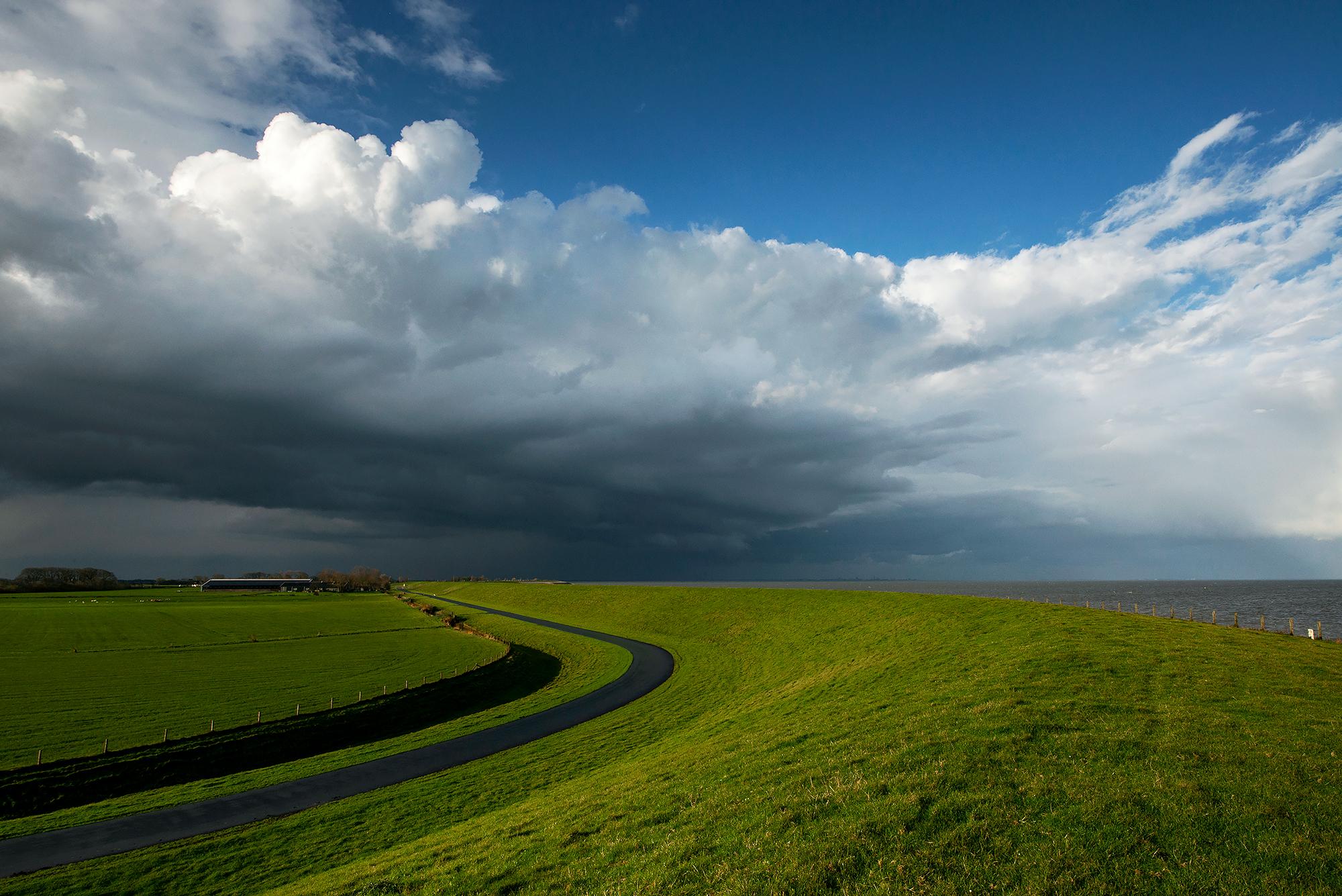 Grote wolkenlucht strekt zich uit boven de polders en dijk bij het dorpje Vatrop op het voormalige Waddeneiland Wieringen