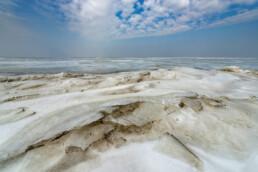 IJs op bevroren, ondiepe delen van de Waddenzee tijdens winter op het voormalige Waddeneiland Wieringen