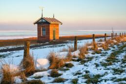 Warme gloed van zonsopkomst schijnt op peilschaalhuisje aan de rand van de Waddenzee op Wieringen