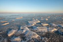 Stukken ijs op bevroren water van Waddenzee tijdens zonsopkomst op Wieringen