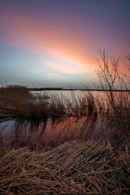 Rode gloed op wolken tijdens een koude zonsopkomst bij Ham en Crommenije in Uitgeest
