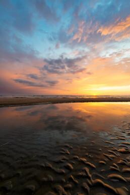 Weerspiegeling wolkenlucht in het ondiepe water van een zwin tijdens zonsondergang op het strand van Bloemendaal aan Zee