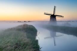 Molen langs het water met mist tijdens zonsopkomst in de polder bij Egmond aan de Hoef