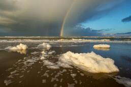 Regenboog en aangespoeld zeeschuim op het strand van Hargen aan Zee