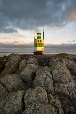 Warm licht van zonsopkomst schijnt op het lichthuis van de Zuidpier bij IJmuiden