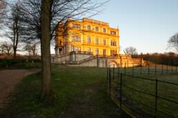 Eerste zonnestralen schijnen op het landhuis tijdens zonsopkomst op Landgoed Elswout in Overveen