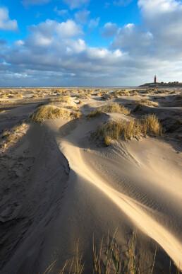 Zonlicht schijnt over duintjes op het strand bij de vuurtoren Eierland op het Waddeneiland Texel