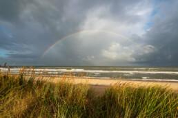 Uitzicht vanaf de duinen op het strand en een regenboog boven zee in het Noordhollands Duinreservaat bij Egmond-Binnen