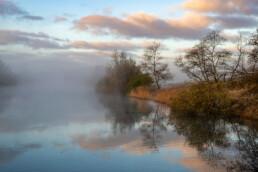 Mistige zonsopkomst aan de oever van een infiltratiekanaal in de Amsterdamse Waterleidingduinen bij Overveen